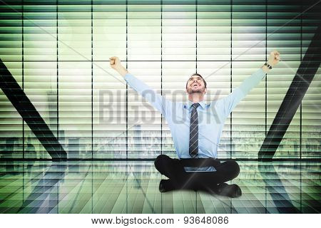 Businessman cheering with tablet sitting on floor against window overlooking city