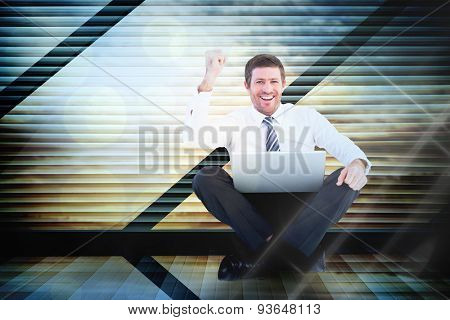 Businessman using laptop and cheering against window overlooking city