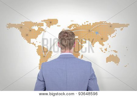 A back turned businessman on a background against world map with lines