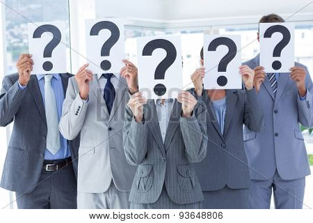 Business colleagues hiding their face with question mark sign at the office