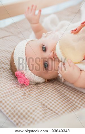 Happy cute baby girl drinking her baby bottle at home in bedroom