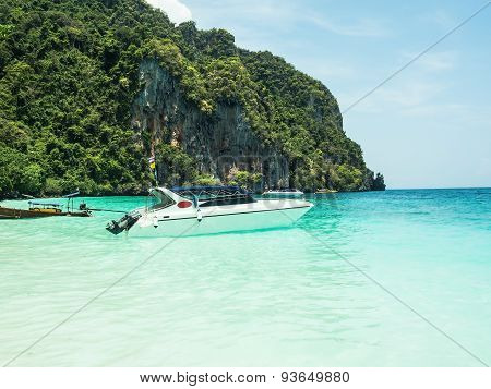 Beautiful island beach with motor boat at Phi Phi island.
