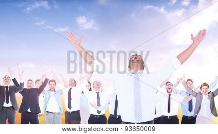 Handsome businessman cheering with arms up against beautiful orange and blue sky