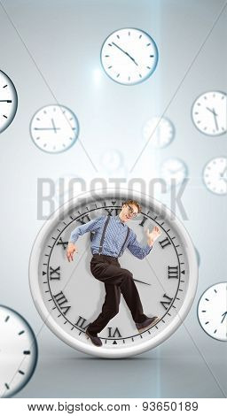 Geeky hipster walking and looking at camera against digitally generated floating clock pattern