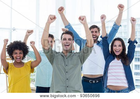 Young creative business people gesturing arm up at office