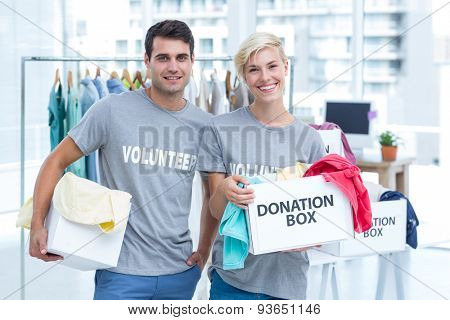 Happy volunteer couple holding donation boxes