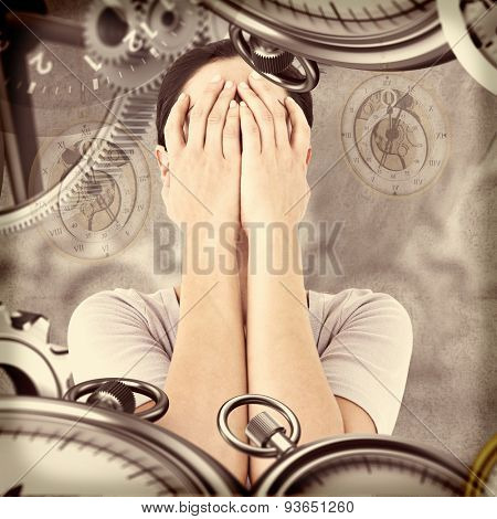 Sad woman hiding her face against grey background