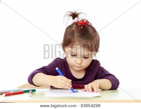 Keen little girl draw with felt-tip pen sitting at the table