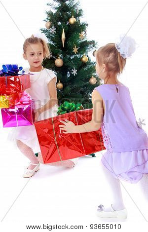 Girls sisters around the Christmas tree fuss considering boxes w