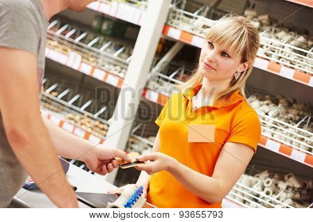 Hardwarre seller or sale assistant cashier accepting credit card as payment for purchase