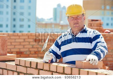 construction worker. Portrait of mason bricklayer installing red brick with trowel putty knife outdoors