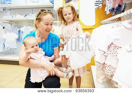 woman choosing children apparel with little baby and child girl on hands in clothing shop supermarket
