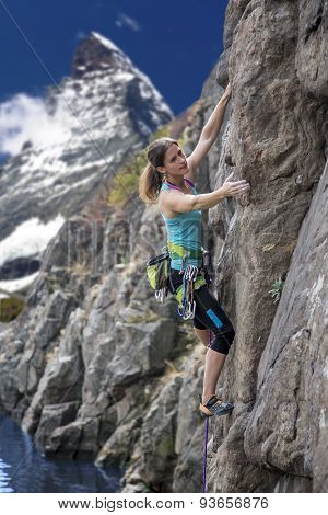 Elegant female alpine climber ascents natural rock
