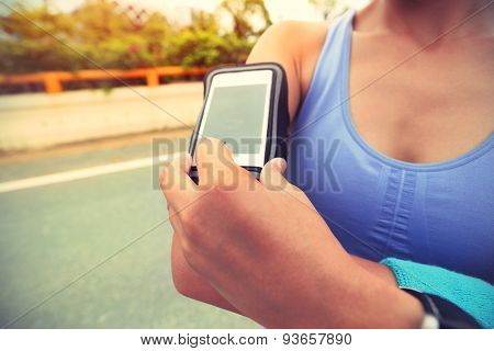 Runner athlete listening to music from smart phone mp3