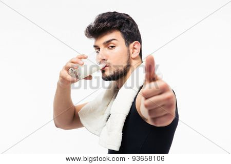 Fitness man drinking milk and showing thumb up isolated on a white background