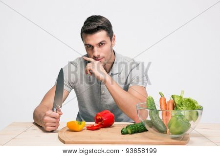 Handsome man sitting at the table and preparing salad over gray background