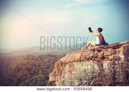 woman hiker taking photo with digital tablet at mountain peakvintage effect