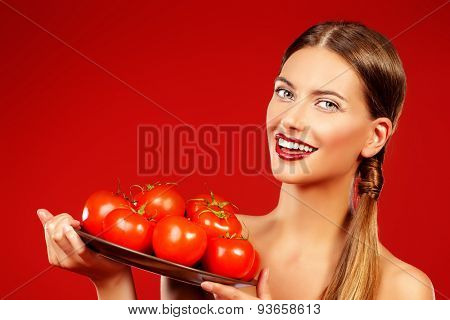 Beautiful smiling young woman holding a dish with ripe juicy tomatoes. Red background. Healthy eating concept.