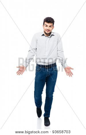 Full length portrait of a casual young man walking and shrugging shoulders isolated on a white background. Looking at camera