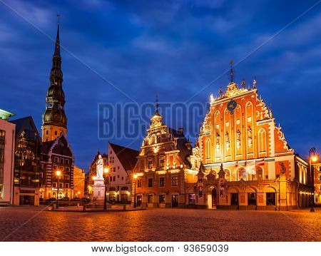 Riga Town Hall Square, House of the Blackheads, St. Roland Statue and St. Peter's Church illuminated in the night, Riga, Latvia