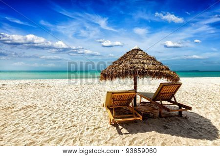 Vacation holidays background wallpaper - two beach lounge chairs under tent on beach