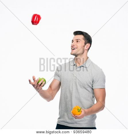 Happy young man juggling pepper isolated on a white background
