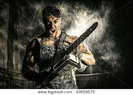 Shouting muscular man with a chainsaw over dark grunge background.