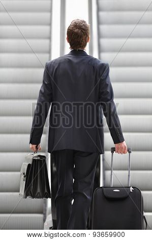 Businessman on escalator with bag and trolley, business travel
