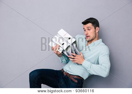 Young man holding folders over gray background