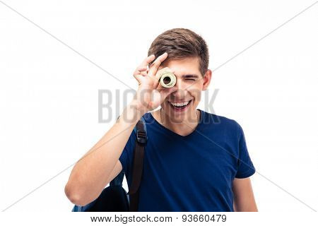 Smiling male student looking at camera through money isolated on a white background