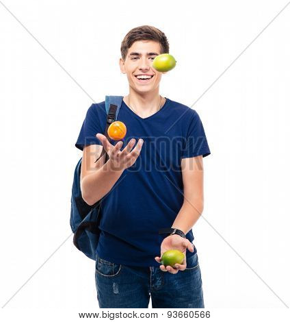 Casual young man juggles with fruits isolated on a white background