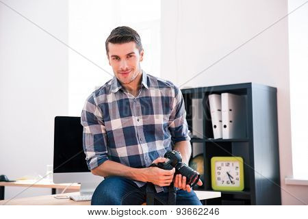Smiling handsome man sitting on the table and holding photo camera in office