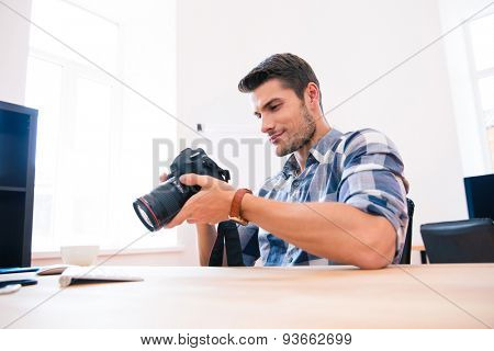 Casual happy young man sitting at the table with photo camera