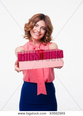 Smiling young woman giving gift box on camera isolated on a white background