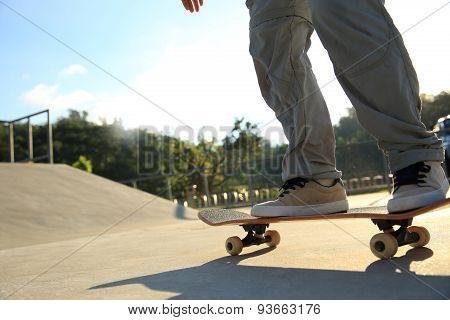 young woman skateboarding at skatepark
