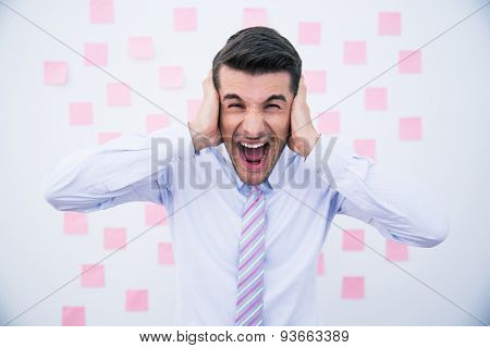 Businessman covering his ears and shouting in office