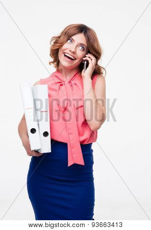Smiling businesswoman talking on the phone and holding folders isolated on a white background. Looking up