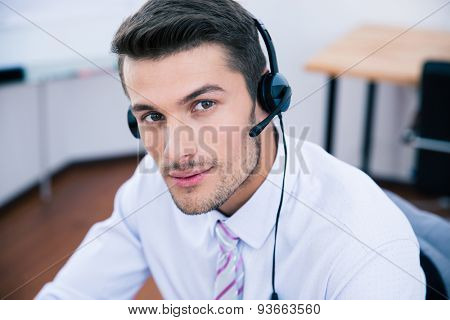 Portrait of a handsome male operator with headset looking at camera in office