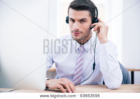 Confident male operator sitting at his workplace in office and looking at camera