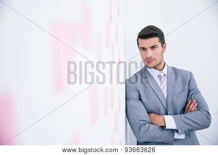 Confident businessman with arms folded leaning on the wall with stickers in office