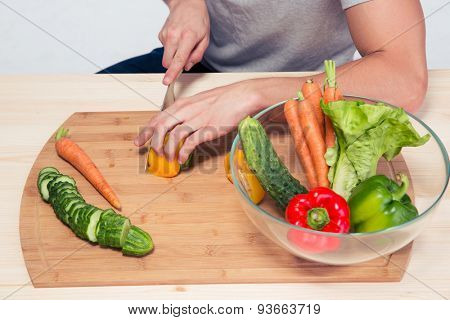 Closeup image of a male hands preparing salad on wooden board