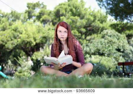 Student Sitting In The Park With A Book Looking Up