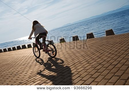 Girl rides a bike on the promenade by the sea at sunset. Focus on the pavement. On image superimposed filter Color Lookup.