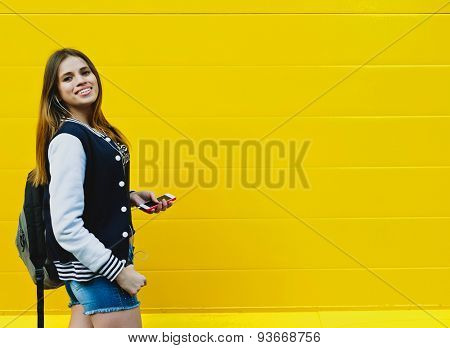 Happy young girl listening music  in headphones over yellowwall