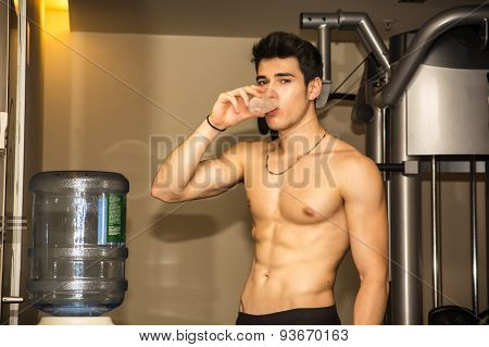 Attractive athletic young man drinking water in gym