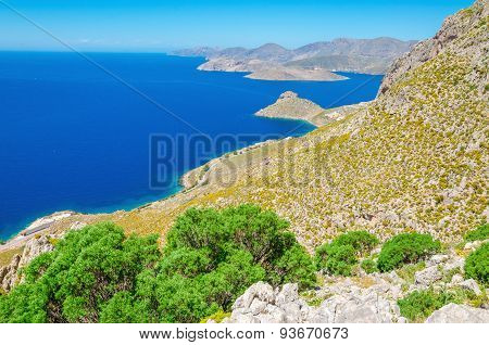Greek bay with green bushes and blue sky, Greece