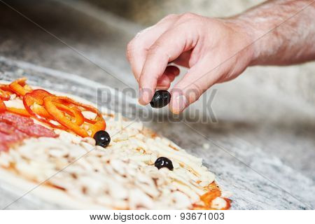 hand of chef baker in uniform adding ingredients into pizza during pizza preparation at restaurant kitchen
