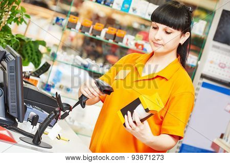 female seller with bar code scanner scanning lamp at store