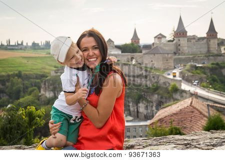 Mom and son travel. They stand on the bridge in the background medieval, ancient city