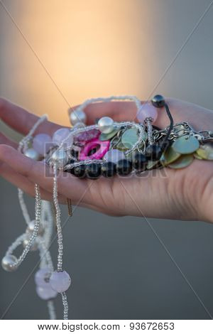 Assortment of jewelry in woman hand, macro photo.